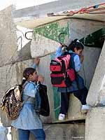 Two girls negotiate a low-point in the section of the Apartheid Wall near Abu Dis, in order to get to school on the other side.