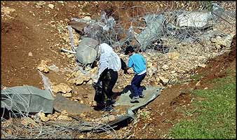 A mother and child on their way home take a route bypassing the checkpoint, through a temporary breach in the roll of barbed wire crossing their right-of-way.