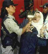 A Palestinian woman is clubbed in the face as she is arrested by Israeli soldiers.