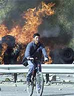 A Bolivian on a bicycle rides past burning cars during one of the recent anti-government riots in the capital.