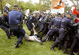 Police carry away a protestor as others control a crowd of anti-war demonstrators outside the USA embassy in Canberra.