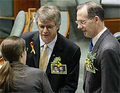 Green Party Senator Bob Brown and MP Michael Organ talk with Senator Kerry Nettle whilst wearing pictures of the two Australian citizens being held at Guantanamo Bay.