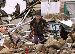 A Palestinian child cries as he recovers a homemade toy from the rubble of his destroyed house in Rafah, Gaza Strip.