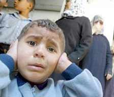 A disturbed Palestinian child covers his ears after an Israeli warplane fired a missile on a car in Zeitoun.