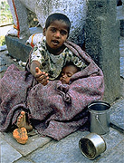 This boy, whose worldly possessions are two mess-cans, asks the photographer to throw him a few coins.