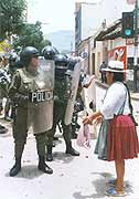 An indigenous Bolivian confronts a line of armed police during protests against globalisation in the country.