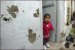 A terrorised child stands in the bullet-ridden doorway of his home in Samarra, after the latest USA raids on the town?s inhabitants leave eight dead.
