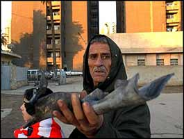 An Iraqi shows shrapnel left after the latest resistance strike near his home in Baghdad.