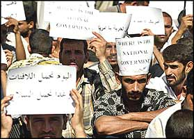 Iraqis demonstrating against the occupation hold paper notices, saying 'Where is the National Government?', and in Arabic, 'Today we carry paper, tomorrow it will be guns.'