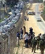 A long line of Palestinian car drivers wait, while an Isreali car cruises down an empty 'Jewish' road.