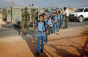 Every day the children of Jubara must wait for the soldiers to allow them through the checkpoint, then walk in a line past soldiers armed with machine guns, to go to school.