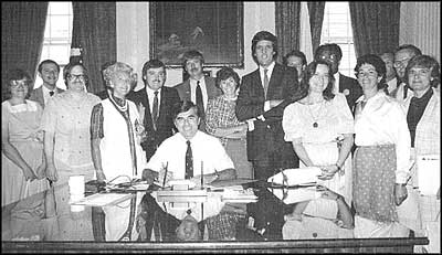 Supporters of the 'Rally Round the Quabbin Acid Rain Proclamation', August 1984, at the signing by Governor Michael Dukakis. Lt. Governor John Kerry stands behind Dukakis, and to Kerry's left is Genevieve Cora Fraser.