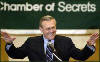 Donald Rumsfeld says that there are an unknown quantity of WMDs in one of his hands. We have to guess which one.